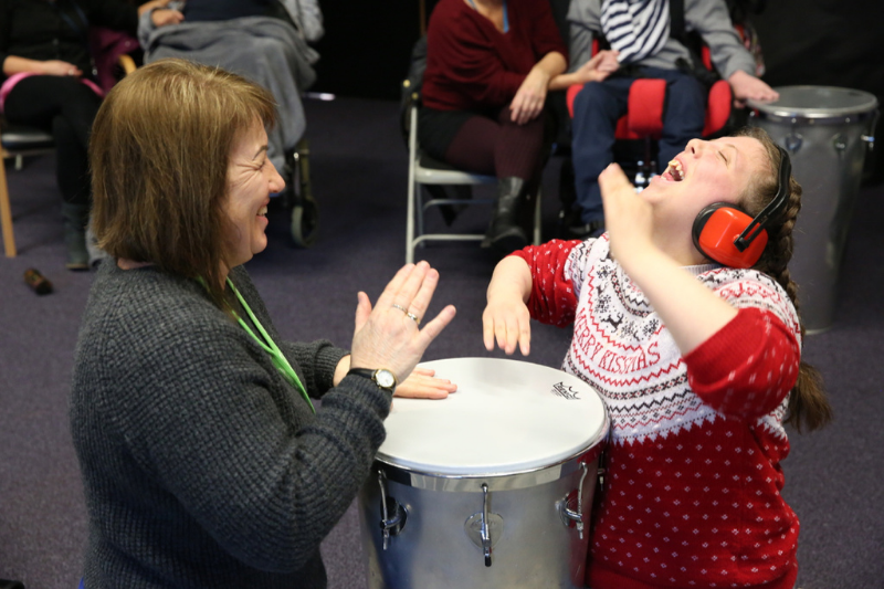 Student and staff laughing playing samba drum