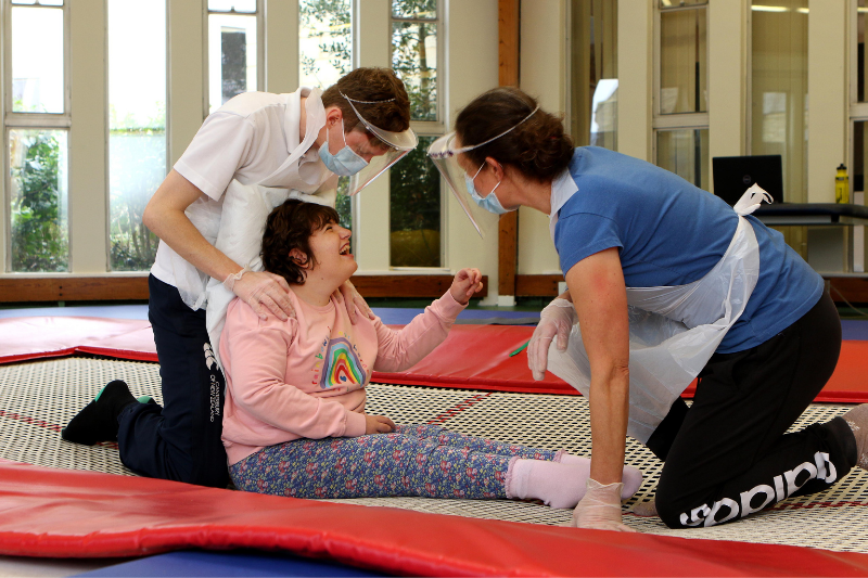 Student smiling on trampoline with physiotherapists