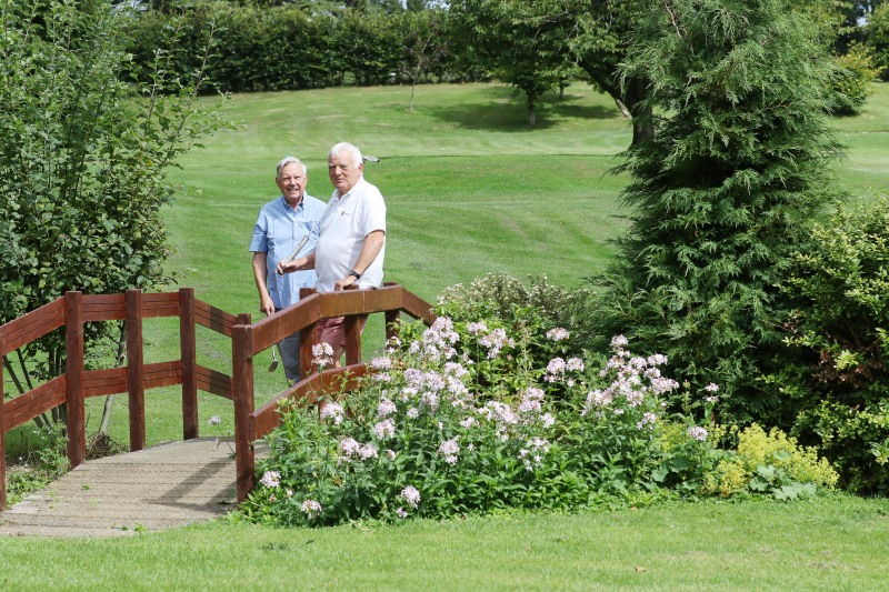 Two male golfers stop to admire the view as they cross a wooden bridge at StarGolf