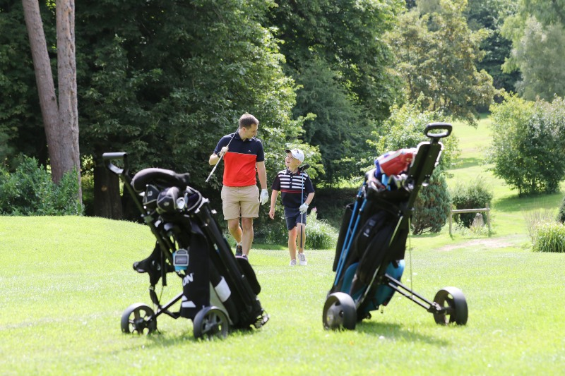 Father and son walk back towards their golf trolleys at StarGolf