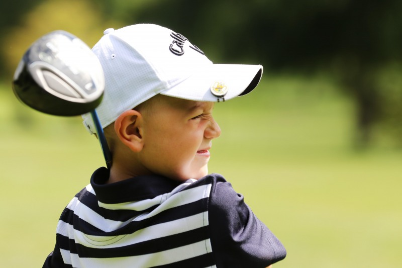 Young male golfer looks into the distance after his shot