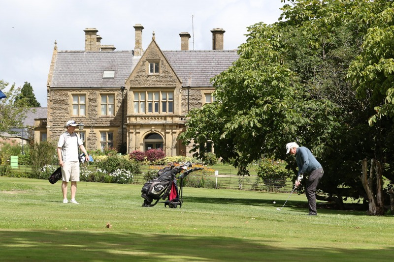 A team of three golfers prepare for their next shot in front of Ullenwood Manor