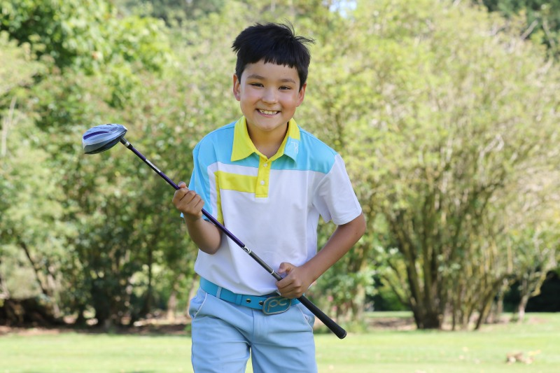 Young male golfer excitedly holds onto his golf club