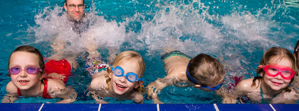 A young girls wearing goggles in the National Star swimming pool looks up to the camera smiling.