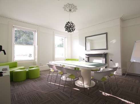 Meeting room with white and lime colour chairs and table.