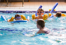 Three young children swimming with armbands and floats in the National Star swimming pool.