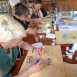 Four staff and students sit together at a desk creating Turkish tradition art design paintings