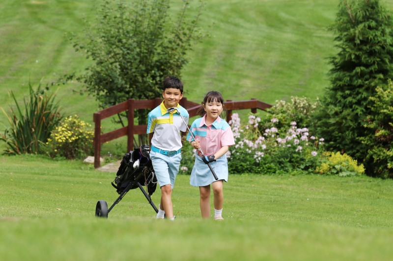 Young brother and sister on the fairway with their golf trolley at StarGolf