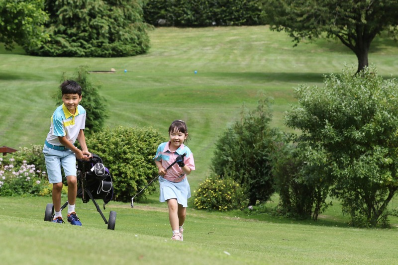 Brother and sister walk towards their next hole pulling a golf trolley