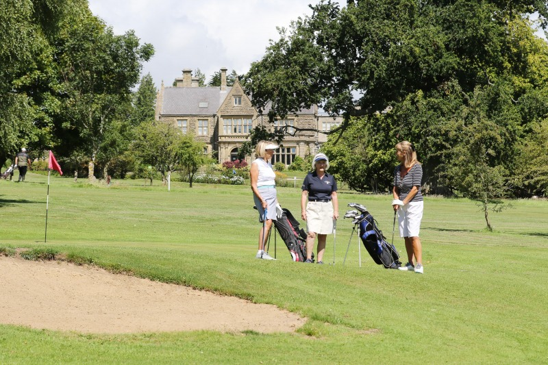 Women golfers stop for a chat on the fairway at StarGolf in front of Ullenwood Manor