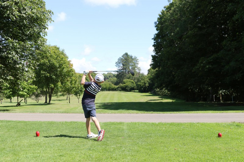 Young male golfer takes a shot