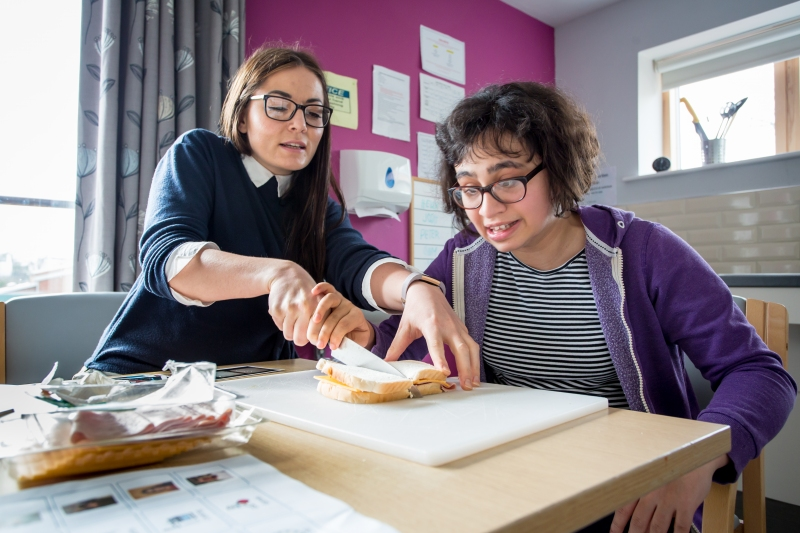Student being shown how to make a sandwich by a member of staff