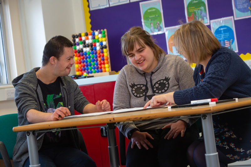 Student working with a tutor in a classroom at National Star in Hereford