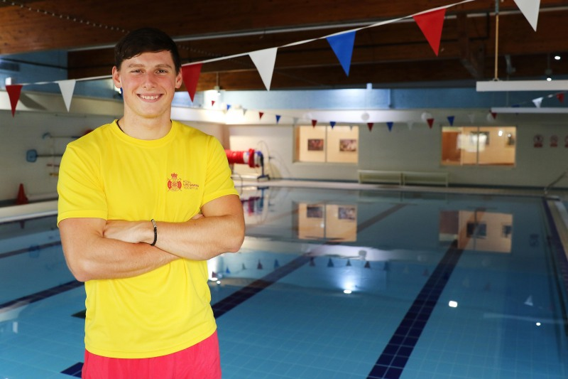 National Star Lifeguard standing by the side of a pool