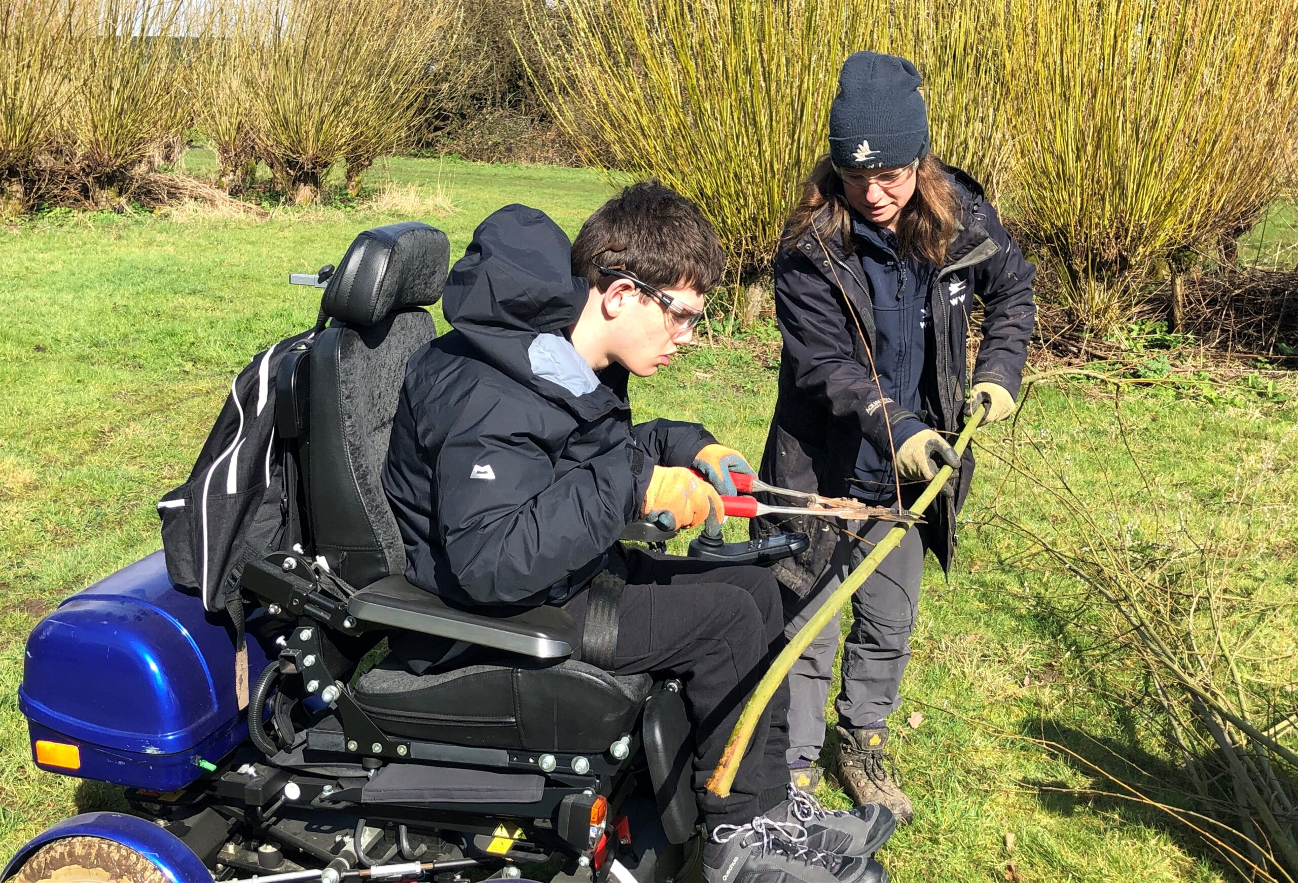 Elliot cutting a tree with help of a mentor at Slimbridge