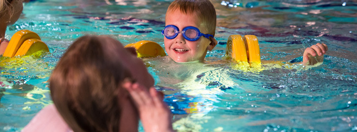 A young boy swimming with armbands in the National Star swimming pool.