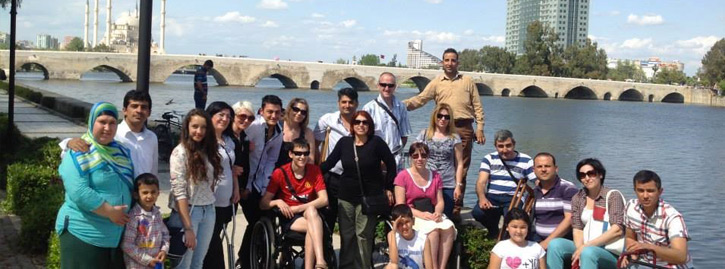 A group of international students and staff pose of a photo together in front of a bridge.