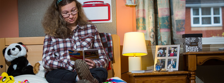 A National Star College student sat on her bed reading a book.