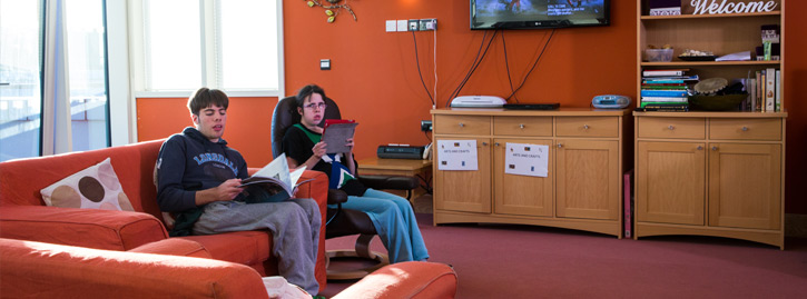 Two National Star College students reading in the Lounge.