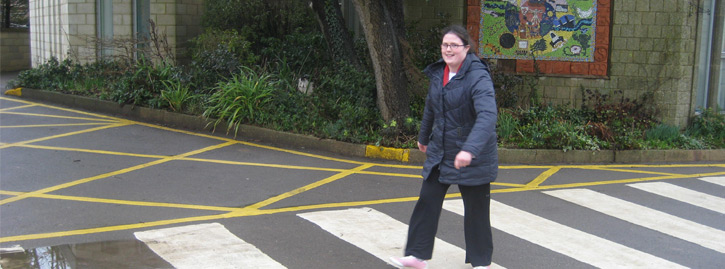 Sophie who is a lift learner crosses on a zebra crossing.