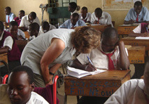 A female member of staff from National Star talks with a pupil from Joyland school in Kenya, whilst they are sat at their desk