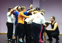 A photograph taken during a dance performance where a group of dancers are huddled together facing a man knelt on the floor