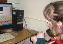 A female learner using IT access tools to access a computer whilst sat at a desk