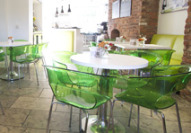 Main dining area in Star Bistro pepper crescent; green chairs and white tables on a tiled floor