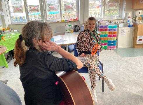 Demi smiling and taking part in music therapy using an instrument