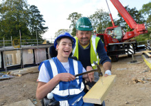 National Star College student standing next to construction worker holds hammer.