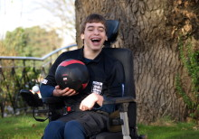 Nathen Mattick sat in his chair smiling and holding a football