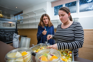 National Star student serving fruit into bowls