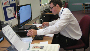 Man in a white shirt working at a computer.