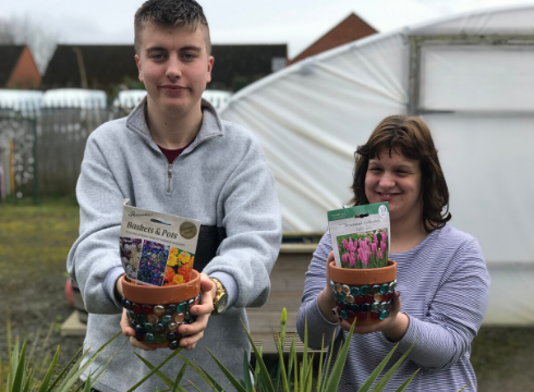 Students holding flowerpots ready to plant seeds near the polytunnel at National Star in Hereford