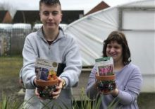 Students in Hereford holding flowerpots ready to plant seeds