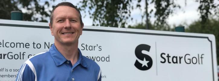 Professional golfer Paul Johnson smiling in front of StarGolf signpost