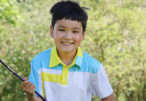 Young golfer smiling holding golf club