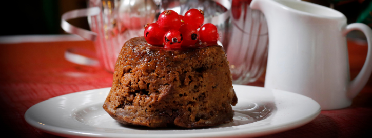 Christmas pudding sat on white plate with milk jug and christmas accessories in the background
