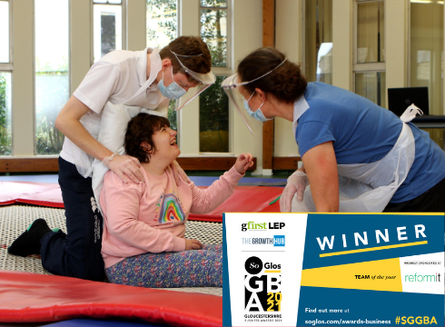 Two therapists working with a smiling student and Team of the Year banner