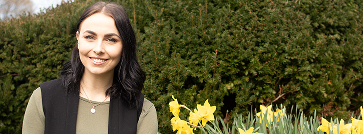 Hannah Bernard smiling stood next to a field of dandelions