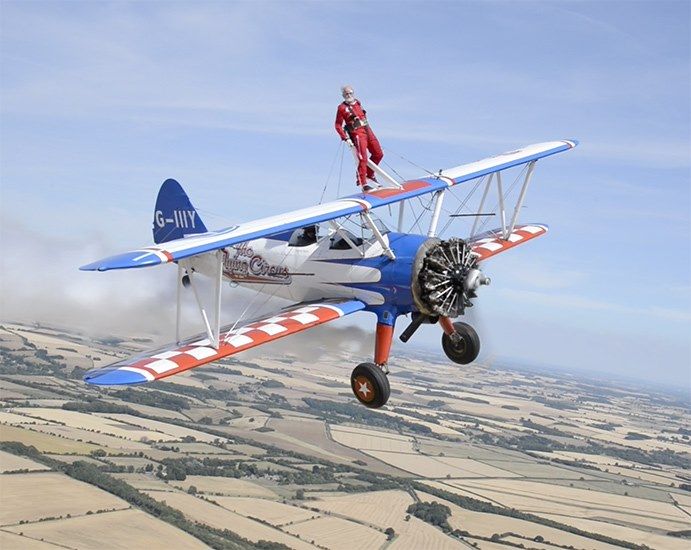 Man stood on the wing of an aeroplane doing the wing walk