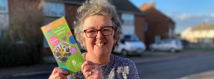Alison smiling holding a National Star lottery leaflet