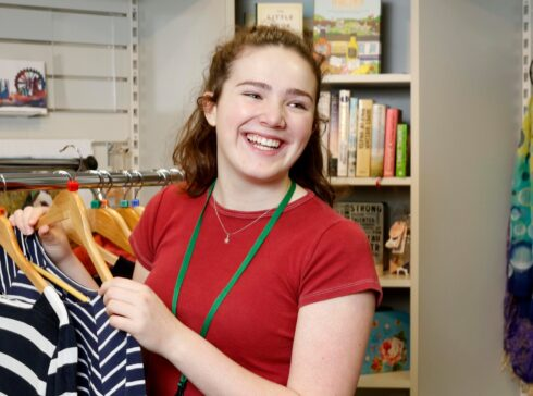 Volunteer smiling with clothing on hanger in charity shop
