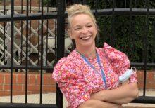 Female member of staff smiling as she leans on railings