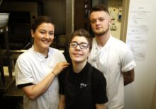 Young person with a disability smiling as the camera as two chefs look on