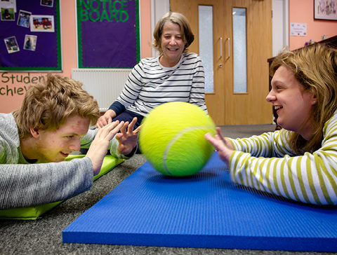 Two students and teacher passing large tennis ball