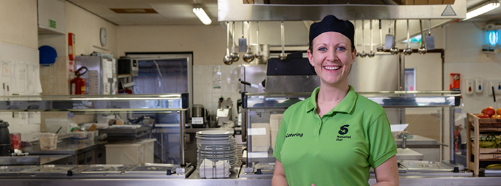 Female staff member in front of professional kitchen
