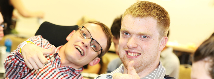 Two male students with thumbs up